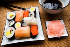 Assorted sushi on plate. Sushi settings: maki-suhi, unagi-sushi, sushi with caviar of flying fish, chops, plates, soya sauce, ginger stock photo