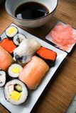 Assorted sushi on plate. Sushi settings: maki-suhi, unagi-sushi, sushi with caviar of flying fish, chops, plates, soya sauce, ginger royalty free stock photos