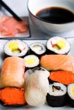 Assorted sushi on plate. Sushi settings: maki-suhi, unagi-sushi, sushi with caviar of flying fish, chops, plates, soya sauce, ginger royalty free stock images
