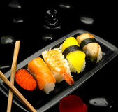 Assorted sushi plate. On black pebbles over black background Stock Photos