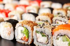 Assorted sushi rolls on black background Royalty Free Stock Photography