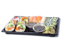 Assorted sushi rolls in a black plastic tray. Against white background stock images