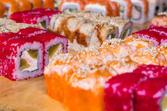 Assorted sushi and rolls on wood board in dark light Stock Image