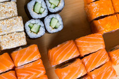 Assorted sushi and rolls on wood board in dark light Royalty Free Stock Photos