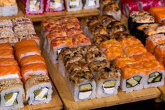 Assorted sushi and rolls on wood board in dark light Stock Photo