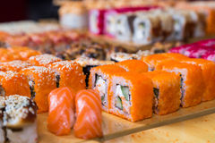 Assorted sushi and rolls on wood board in dark light Stock Photos