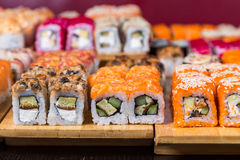 Assorted sushi and rolls on wood board in dark light Royalty Free Stock Photography