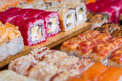 Assorted sushi and rolls on wood board in dark light Royalty Free Stock Image