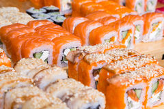 Assorted sushi and rolls on wood board in dark light Royalty Free Stock Photo