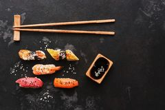 Assorted sushi set on a black stone background. Japanese food sushi, soy sauce, chopsticks. Top view, copy space.  stock images