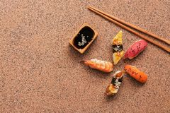 Assorted sushi set on a brown stone background. Japanese food sushi, soy sauce, chopsticks. Top view, copy space.  royalty free stock images