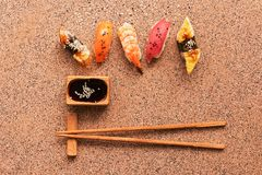 Assorted sushi set on a brown stone background. Japanese food sushi, soy sauce, chopsticks. Top view, copy space.  stock photo