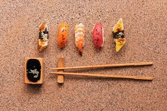 Assorted sushi set on a brown stone background. Japanese food sushi, soy sauce, chopsticks. Top view, copy space.  stock image