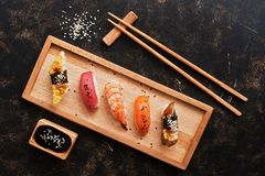 Assorted sushi set on a dark rustic background. Japanese food sushi on a wooden plate, soy sauce, chopsticks. Top view
