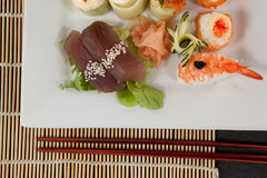 Assorted sushi set served with chopsticks in white plate on sushi mat Royalty Free Stock Photos