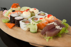 Assorted sushi set served in wooden boat plate Royalty Free Stock Image