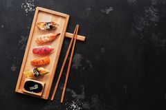 Assorted sushi set on a wooden plate, dark stone background. Japanese food sushi, soy sauce, chopsticks. Top view, copy space.  stock images