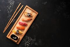 Assorted sushi set on a wooden plate, dark stone background. Japanese food sushi, soy sauce, chopsticks. Top view, copy space.  royalty free stock image