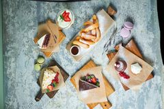 Assorted sweet desserts. Top view. Gray textured background. Beautiful serving dishes. Dessert. Food chain. Assorted sweet desserts: cake, churos, meringue roll royalty free stock photo
