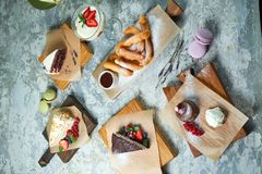 Assorted sweet desserts. Top view. Gray textured background. Beautiful serving dishes. Dessert. Food chain. Assorted sweet desserts: cake, churos, meringue roll royalty free stock image