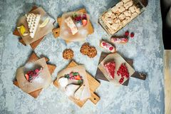 Assorted sweet desserts. Top view. Gray textured background. Beautiful serving dishes. Dessert. Food chain. Assorted sweet desserts: cake, churos, meringue roll stock images