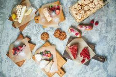 Assorted sweet desserts. Top view. Gray textured background. Beautiful serving dishes. Dessert. Food chain. Assorted sweet desserts: cake, churos, meringue roll stock photo