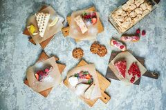Assorted sweet desserts. Top view. Gray textured background. Beautiful serving dishes. Dessert. Food chain. Assorted sweet desserts: cake, churos, meringue roll royalty free stock photography