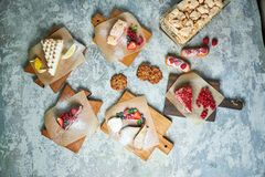Assorted sweet desserts. Top view. Gray textured background. Beautiful serving dishes. Dessert. Food chain. Assorted sweet desserts: cake, churos, meringue roll stock photos