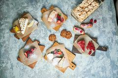 Assorted sweet desserts. Top view. Gray textured background. Beautiful serving dishes. Dessert. Food chain. Assorted sweet desserts: cake, churos, meringue roll royalty free stock images