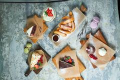 Assorted sweet desserts. Top view. Gray textured background. Beautiful serving dishes. Dessert. Food chain. Assorted sweet desserts: cake, churos, meringue roll royalty free stock photos