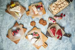 Assorted sweet desserts. Top view. Gray textured background. Beautiful serving dishes. Dessert. Food chain. Assorted sweet desserts: cake, churos, meringue roll stock image