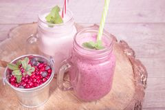 Assorted fruit or berry shakes on white table. Smoothie concept. Assorted t or berry milk shakes in mason jar on wooden desk and table. Smoothie healthy eating Royalty Free Stock Image