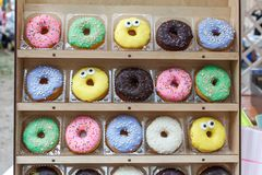 Assorted tasty colorful donuts on wooden showcase, close up view Royalty Free Stock Photography