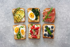 Assorted toasts with eggs, ham ,vegetables and fruits served on Royalty Free Stock Images