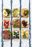 Assorted toasts with eggs, ham ,vegetables and fruits served on Royalty Free Stock Photos