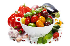 Assorted tomatoes and vegetables in colander Stock Image