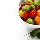 Assorted tomatoes and vegetables in colander Stock Photography