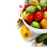 Assorted tomatoes and vegetables in colander Stock Photo