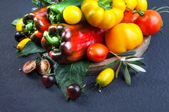 Assorted tomatoes and vegetables on dark background. Photo for y stock photo