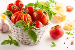 Free Assorted Tomatoes With Basil In Basket, Garlic, Spice And Raw Pasta For Italian Cuisine. Healthy Food Concept On White Background Royalty Free Stock Image - 190564166