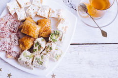 Assorted traditional eastern desserts. And cup of tea on a white wooden background. Baklava, halva, rahat lokum, sherbet, nuts, dates, kadayif on plates. Top Stock Images
