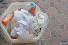 Assorted trash in a plastic bin with paper and plastic bags whic Stock Image