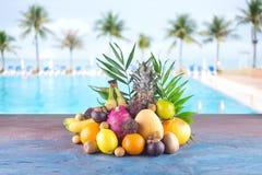 Assorted tropical fruits on the beach orange , pineapple, lime, mango, dragon fruit, orange, banan, rambutan and lichi. Group of exotic tropical fruits royalty free stock photo