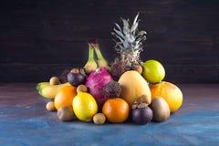 Assorted tropical fruits, orange,Ananas or pineapple, lime,mango, dragon fruit, orange, banan, rambutan and lichi on. Dark background. Copy space royalty free stock photography
