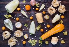Assorted types of yellow hued vegetables. top wiev. Of pepper, corn, parsley, tomatoes, carrots, pasta, onions, zucchini on dark wooden background. Concept of Royalty Free Stock Photography