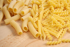Assorted varieties of dried pasta. Assorted varieties of italian dried pasta on a wooden table Royalty Free Stock Photo
