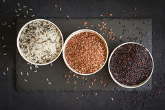 Assorted of variety of gourmet rice in bowls On black background. Top view Stock Photo