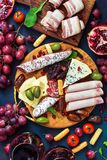 Assorted variety of snacks with red wine. Various sausages and cold meat, cheese with mold, fruit. Top view, flat lay royalty free stock photography