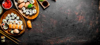 Assorted variety of sushi, rolls and Maki on the plates. On dark rustic background stock photography