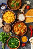 Assorted various Indian food on a dark rustic background. Traditional Indian dishes - Chicken tikka masala, palak paneer, saffron